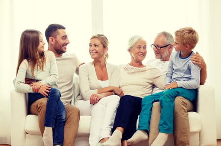family, happiness, generation and people concept - happy family sitting on couch at homeの写真素材