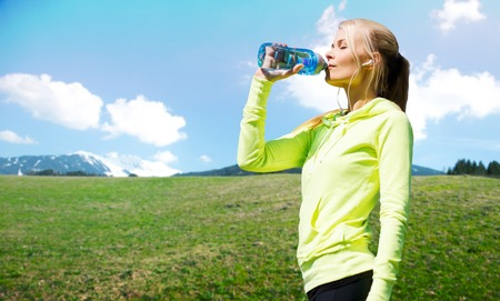 people, fitness, sport and healthy lifestyle concept - happy woman drinling water from bottle after workout over natural background