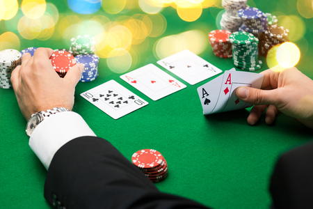 casino, gambling, poker, people and entertainment concept - close up of poker player with playing cards and chips at green casino table over holidays lights background