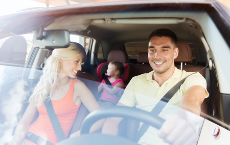 Foto de family, transport, safety, road trip and people concept - happy man and woman with little child driving in car - Imagen libre de derechos