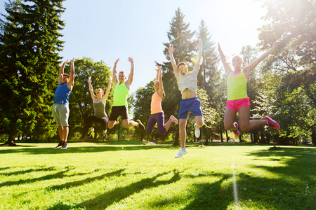 Foto de fitness, sport, friendship and healthy lifestyle concept - group of happy teenage friends jumping high outdoors - Imagen libre de derechos