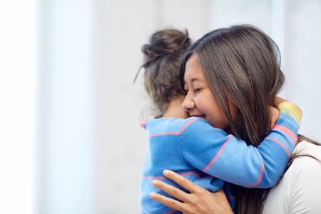 Foto de family, children, love and happy people concept - happy mother and daughter hugging at home - Imagen libre de derechos