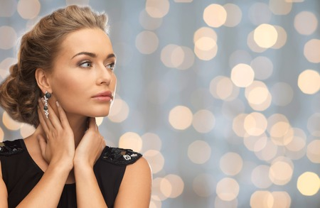 Photo pour people, holidays and glamour concept - beautiful woman wearing earrings over lights background - image libre de droit