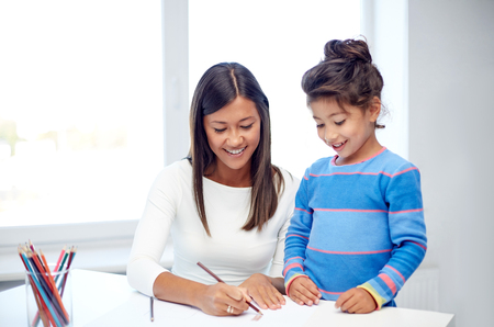 Photo for family, children, creativity and happy people concept - happy mother and daughter drawing with pencils at home or kindergarten - Royalty Free Image