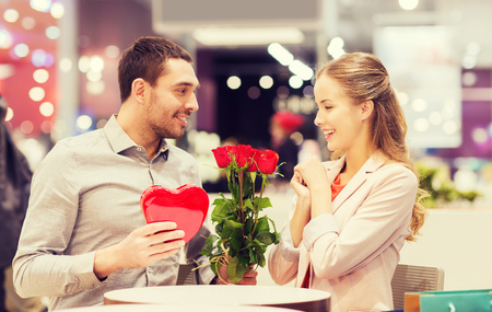 Photo pour love, romance, valentines day, couple and people concept - happy young man with red flowers giving present to smiling woman at cafe in mall - image libre de droit