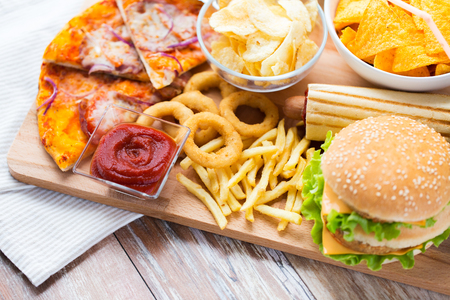 fast food and unhealthy eating concept - close up of hamburger or cheeseburger, deep-fried squid rings, french fries, pizza and ketchup on wooden table top view