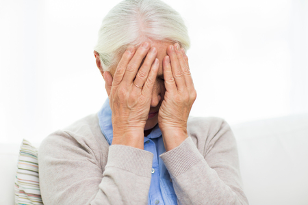 health care, pain, stress, age and people concept - senior woman suffering from headache or grief