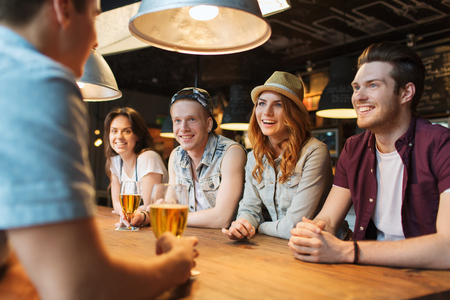 Photo pour people, leisure, friendship and communication concept - group of happy smiling friends drinking beer and talking at bar or pub - image libre de droit