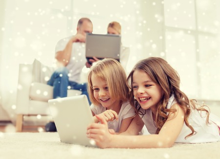Foto de family, home, technology and people - smiling mother, father and little girls with tablet pc computer over snowflakes background - Imagen libre de derechos
