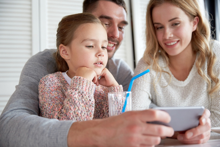 Photo pour family, parenthood, technology and people concept - happy mother, father and little girl with smartphone having dinner at restaurant - image libre de droit
