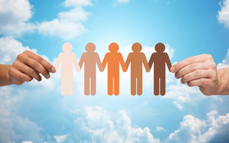 Foto de community, unity, population, race and humanity concept - multiracial couple hands holding chain of paper people pictogram over blue sky and clouds background - Imagen libre de derechos