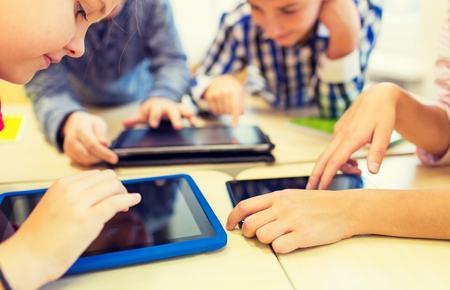 Foto de close up of school kids with tablet pc computers having fun and playing on break in classroom - Imagen libre de derechos