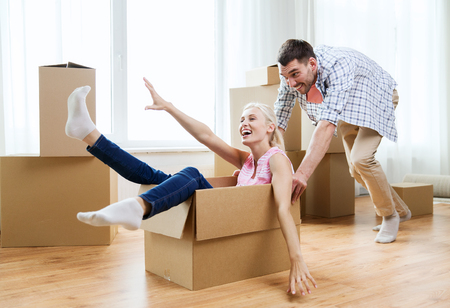 Photo pour happy couple having fun and riding in cardboard boxes at new home - image libre de droit