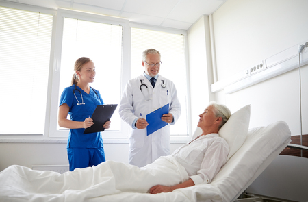 doctor and nurse with clipboards visiting senior patient woman at hospital ward