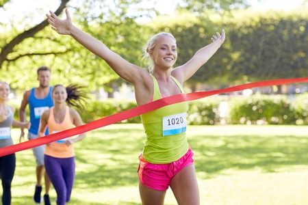Photo pour fitness, sport, victory, success and healthy lifestyle concept - happy woman winning race and coming first to finish red ribbon over group of sportsmen running marathon with badge numbers outdoors - image libre de droit
