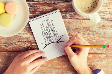 Photo pour creativity, imagination, inspiration and people concept - close up of female hands drawing with pencil in notebook, coffee and cookies on table - image libre de droit
