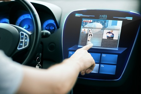 Photo pour transport, modern technology, mass media and people concept - male hand pointing finger to monitor on car panel and reading news - image libre de droit