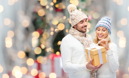 Foto de winter, holidays, couple, christmas and people concept - smiling man and woman in hats and scarf with gift box over lights background - Imagen libre de derechos