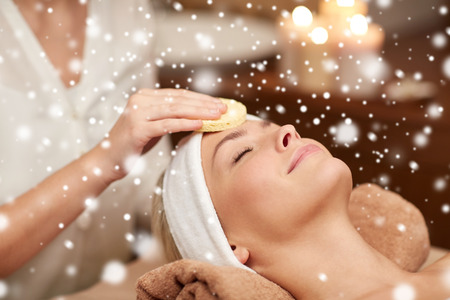 Photo pour people, beauty, spa, cosmetology and relaxation concept - close up of beautiful young woman lying with closed eyes having face cleaning by sponge and beautician hand in spa salon with snow effect - image libre de droit