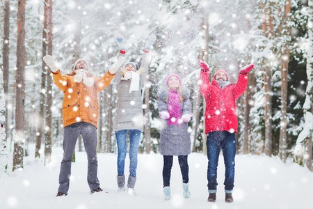 love, season, friendship and people concept - group of happy men and women having fun and playing with snow in winter forest