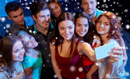 Photo for party, technology, nightlife and people concept - smiling friends with smartphone taking selfie in club and snow effect - Royalty Free Image