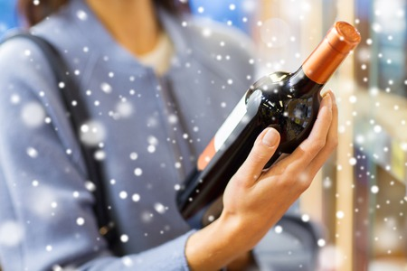 Photo for sale, shopping,  holidays, consumerism and people concept - happy young woman choosing and buying wine in market or liquor store over snow effect - Royalty Free Image
