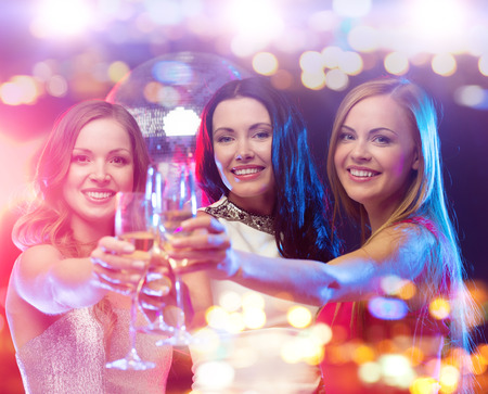 Foto de holidays, nightlife, bachelorette party and people concept - smiling women with champagne glasses at night club - Imagen libre de derechos