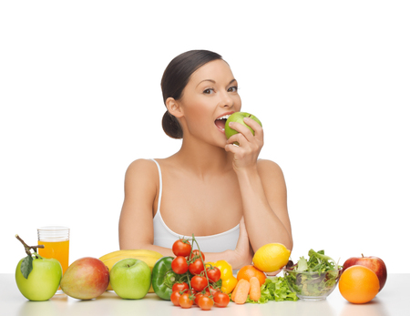 woman eating apple with lot of fruits and vegetables