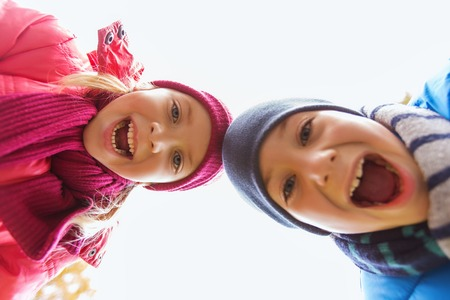 childhood, leisure, friendship, autumn and people concept - happy boy and girl faces outdoors