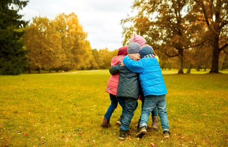 Photo for childhood, leisure, friendship and people concept - group of happy kids hugging in autumn park - Royalty Free Image