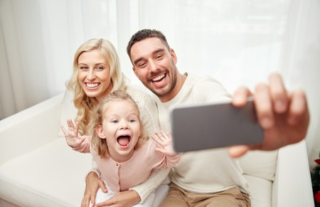 Foto de holidays, technology and people concept - happy family sitting on sofa and taking selfie picture with smartphone at home - Imagen libre de derechos