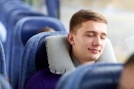 Photo pour transport, tourism, road trip and people concept - happy young man sleeping in travel bus with pillow - image libre de droit
