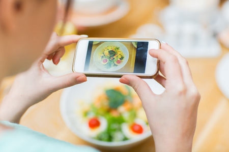 Foto de people, leisure and technology concept - close up of woman hands with smartphone taking picture of food at restaurant - Imagen libre de derechos