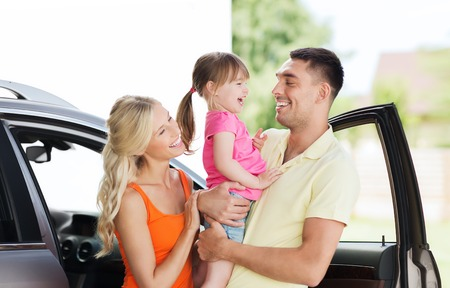 Photo pour family, transport, leisure and people concept - happy man, woman and little girl with car laughing at home parking space - image libre de droit