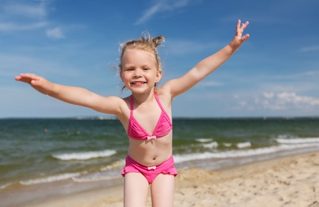 summer, childhood, vacation and people concept - happy little girl in swimwear having fun on beach