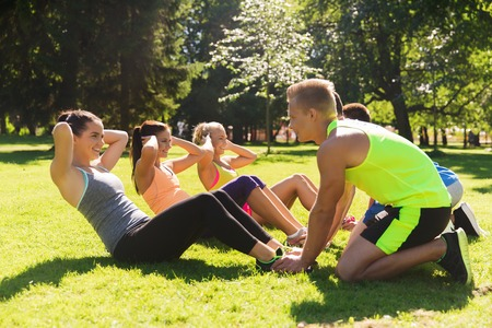 Photo pour fitness, sport, friendship and healthy lifestyle concept - group of happy teenage friends or sportsmen exercising and doing sit-ups at boot camp - image libre de droit