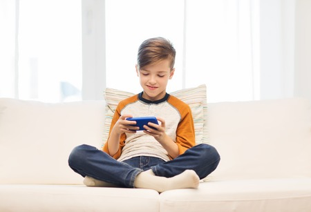 Photo pour leisure, children, technology, internet communication and people concept - smiling boy with smartphone texting message or playing game at home - image libre de droit