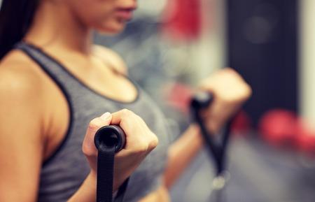 Foto de sport, fitness, lifestyle and people concept - close up of young woman flexing muscles on cable gym machine - Imagen libre de derechos