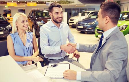 Photo pour auto business, car sale, and people concept - happy couple with dealer shaking hands in auto show or salon - image libre de droit