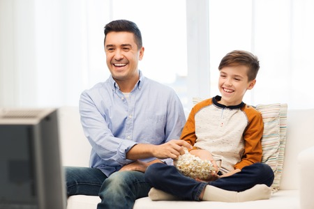 Photo for family, people, technology, television and entertainment concept - happy father and son with popcorn watching tv at home - Royalty Free Image