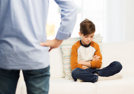 Photo for people, misbehavior, family and relations concept - close up of upset or feeling guilty boy and father at home - Royalty Free Image