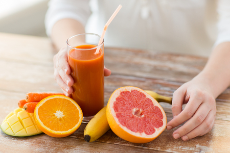 Foto für healthy eating, food, dieting and people concept - close up of woman hands with fruits and fresh juice sitting at table - Lizenzfreies Bild