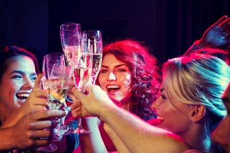 Photo pour party, holidays, celebration, nightlife and people concept - smiling friends with glasses of champagne in club - image libre de droit