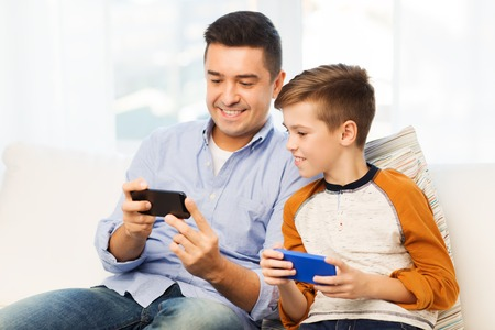 Photo pour leisure, technology, technology, family and people concept - happy father and son with smartphones texting message or playing game at home - image libre de droit