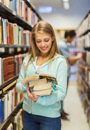 Photo for people, knowledge, education and school concept - happy student girl or young woman with book in library - Royalty Free Image