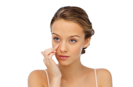 Photo pour beauty, people, cosmetics, skincare and health concept - young woman applying cream to her face - image libre de droit