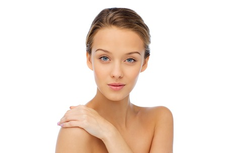 beauty, people, body care and health concept - smiling young woman face and hand on bare shoulderの写真素材