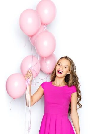 Photo for beauty, people, style, holidays and fashion concept - happy young woman or teen girl in pink dress with helium air balloons - Royalty Free Image