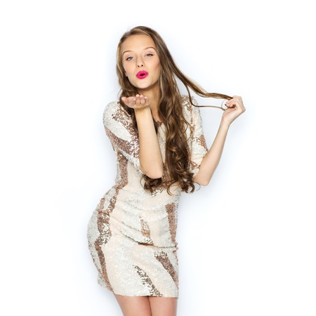 Photo for people, style, holidays, hairstyle and fashion concept - happy young woman or teen girl in fancy dress with sequins and long wavy hair sending blow kiss - Royalty Free Image