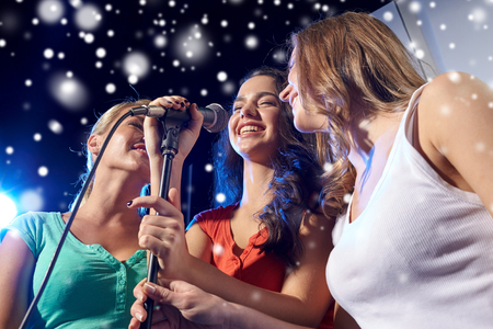 Photo for party, holidays, celebration, nightlife and people concept - happy young women singing karaoke in night club and snow effect - Royalty Free Image